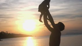 Happy father and daughter playing together dad throwing up his happy daughter at tropical beach at amazing sunset in. Silhouette of happy father and daughter stock video