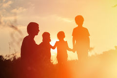 Silhouette of happy father with tree kids at sunset Stock Image