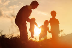 Silhouette of happy father with tree kids at sunset sky Stock Photo