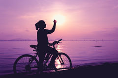 Silhouette of happy female celebrating with arm up towards the s Stock Photos