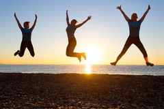 Silhouette of Happy Female jumping in three different positions on beach sunrise Stock Image