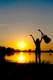 Silhouette of a happy girl with a guitar on a sunrise Stock Image