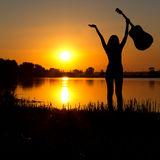 Silhouette of a happy girl with a guitar on a sunrise Stock Photos