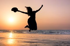 Happy girl jumping on the beach at sunset stock photography