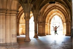 Silhouette of happy girl jumping high up in cloisters of Glasgo. W University. Scotland. Summertime outdoors Stock Image