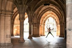 Silhouette of happy girl jumping high up in cloisters of Glasgow. University. Scotland. Europe. Summertime outdoors image Royalty Free Stock Photography