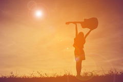Silhouette happy girl playing guitar at the sky sunset, happy ti Royalty Free Stock Photography