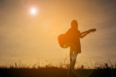 Silhouette happy girl playing guitar at the sky sunset, happy ti Stock Photography