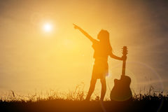 Silhouette happy girl playing guitar at the sky sunset, happy ti Stock Images