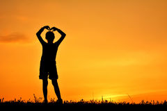 Silhouette of happy girl standing on grass field Stock Photos