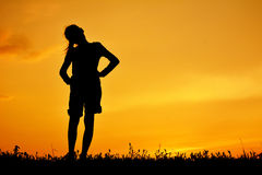 Silhouette of happy girl standing on grass field. And sky sunset stock image