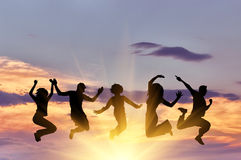 Silhouette of a happy group of people jumping stock photography