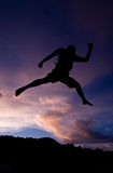Silhouette happy jumping against beautiful in sunset. Freedom, enjoyment concept Royalty Free Stock Image