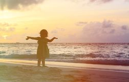 Silhouette of happy little girl with hands up to Stock Photography