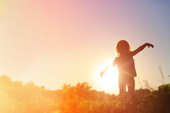Silhouette of happy little girl play at sunset Royalty Free Stock Photo