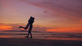 Silhouette of happy loving couple meet and play at the beach on sunset in ocean shore. Silhouette of happy loving couple meet and play at the beach on beautiful Royalty Free Stock Photo