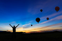 Silhouette happy man against sunset and balloon Royalty Free Stock Photos