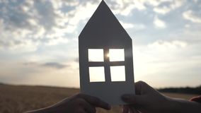 Close-up of hands holding a paper model at home in a field at sunset. Silhouette of a paper house in the rays of the
