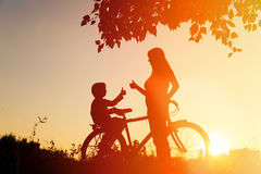 Silhouette of happy mother and son biking at sunset stock photo