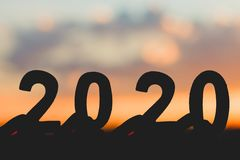 Silhouette 2020 Happy New Year of Hand holding wood number on sky and cloud twilight beautiful nature background