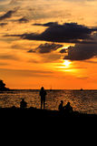 Silhouette of happy people on the beach. At sunset Royalty Free Stock Photo