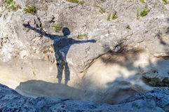 Silhouette of a happy person outdoor on the rocks, with his arms. Silhouette of a happy person on the rocks, with his arms spread, concept of joy, happynes, top Royalty Free Stock Images