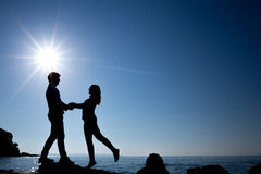 Silhouette of happy teenager couple on the beach Stock Photo