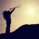 Silhouette of happy tourist with poles in hand above head. Sunny daybreak in mountains. Hiker with sporty backpack Stock Image