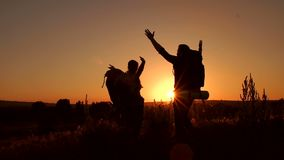 Silhouette of happy tourists on top of mountain. Silhouette of happy tourists who raised his hands up standing on top of a mountain stock video footage