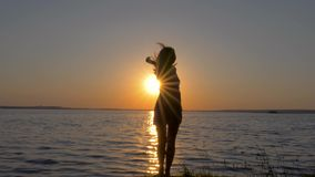 Silhouette Of A Happy Woman Beautifully And Gracefully Dancing At Sunset On Sea. Back view, energetic slender young woman in dress dancing on the beach at sunset stock video footage
