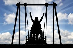 Silhouette of a happy woman is a disabled person in a wheelchair on an adaptive swing for disabled people. The concept of the lifestyle of people with royalty free stock image