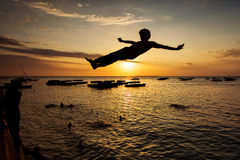 Silhouette of Happy Young boy jumping in water at sunset in Zanz Stock Photography