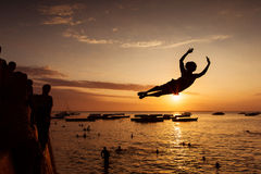 Silhouette of Happy Young boy jumping in water at sunset in Zanz Stock Image