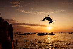 Silhouette of Happy Young boy jumping in water at sunset in Zanz Royalty Free Stock Images