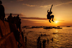 Silhouette of Happy Young boy jumping in water at sunset in Zanz Royalty Free Stock Photos