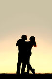 Silhouette of Happy Young Couple Dancing at Sunset Stock Image