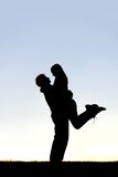Silhouette of Happy Young Couple Hugging Outside at Sunset Royalty Free Stock Photography