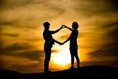 Silhouette of happy young couple outdoors Stock Image
