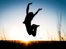 Silhouette of the happy young man who jumps over meadow during s. Unset Stock Photo