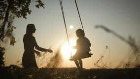 Silhouette of happy young mother and little daughter on a swing at sun light. Pretty girl sitting on a wooden swing and stock footage