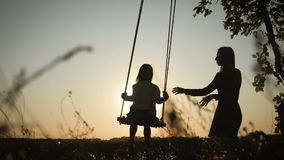 Silhouette of happy young mother and little daughter on a swing at sun light. Pretty girl sitting on a wooden swing and stock video footage