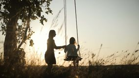 Silhouette of happy young mother and little daughter on a swing at sun light. Pretty girl sitting on a wooden swing and stock video