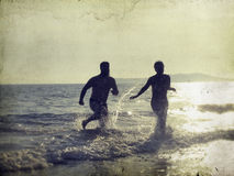 Silhouette of happy young teens playing on the beach Stock Photo