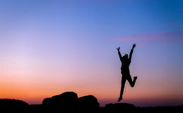 Silhouette of happy young woman against beautiful colorful sky. Stock Images