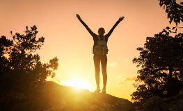 Silhouette of a happy young woman in mountains at sunset stock images