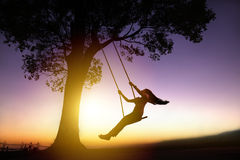 Silhouette of happy young woman on swing. Silhouette of happy young woman on a swing with sunset background royalty free stock image