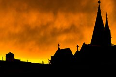 Silhouette of a Harlem rooftop, chimneys, and church steeples, against a bright yellow fiery-looking sky during sunset royalty free stock image