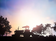 Silhouette Harvesting machine on a farm planted with vegetables, Stock Image