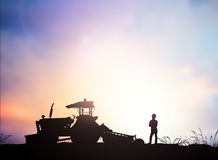 Silhouette Harvesting machine on a farm planted with vegetables, Royalty Free Stock Images