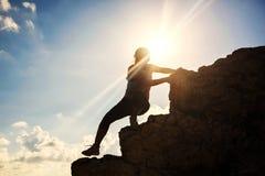 Silhouette woman climbi to hill summit. Silhouette healthy woman climbing up to top hill during sunset. Professional female climber to mountain summit peak Royalty Free Stock Photos